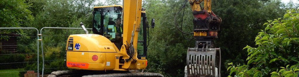 Excavator moving stone for erosion control