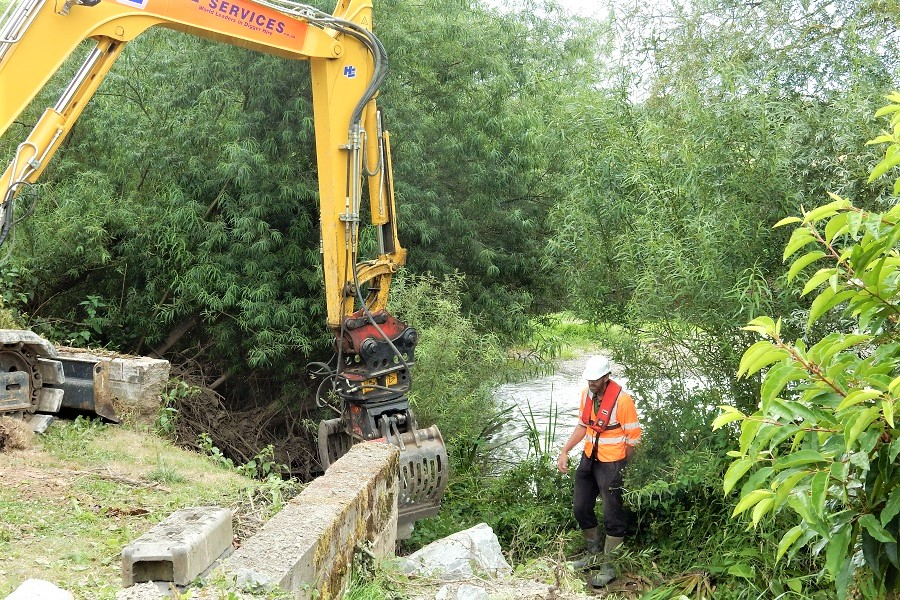 Guiding the excavator in to lay stone along a river bank