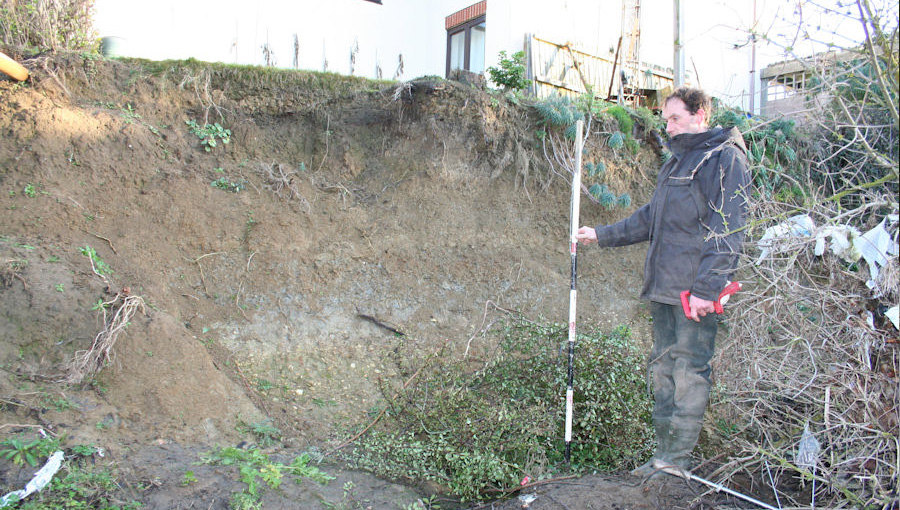 Measuring the bank before installing live willow spiling at a domestic property in Cheltenham