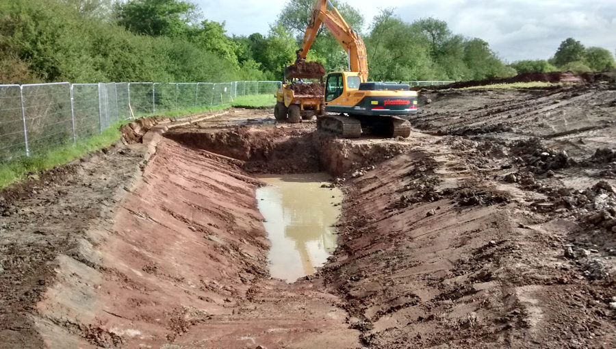 Earthworks to dig channel as part of the great crested newt ponds at the disused airport at Filton, Bristol