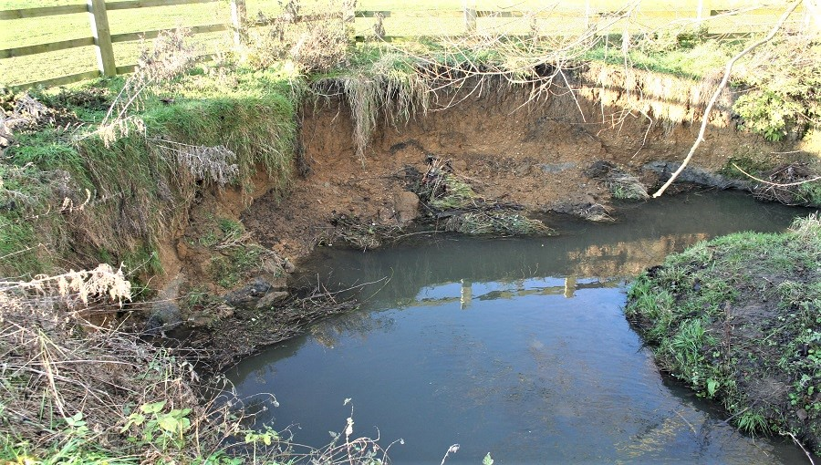 Undercutting of brook bank showing severe soil erosion