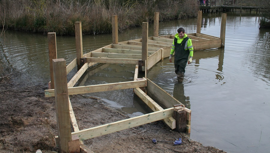 Worker installing a boardwalk over water at The Wetlands Centre, Slimbridge